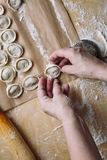 Woman folds the raw dumplings on a sheet of parchment Royalty Free Stock Image