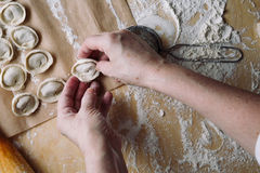 Woman folds the raw dumplings on a sheet of parchment Royalty Free Stock Photography