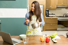 Woman following a cooking tutorial. Good looking young woman following a cooking tutorial online while beating some eggs in a kitchen Royalty Free Stock Image