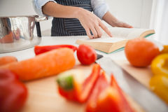 Woman following a recipe in book Royalty Free Stock Image