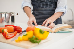 Woman following a recipe in book Royalty Free Stock Images
