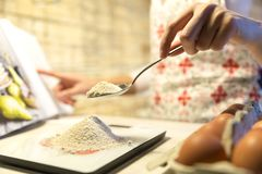 Woman following recipe in cookbook and measuring flour on kitche. N scale Royalty Free Stock Photos