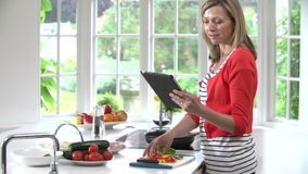 Woman Following Recipe On Digital Tablet Whilst Cooking stock video