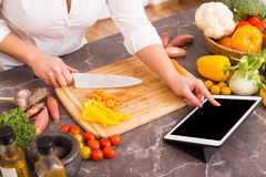 Woman following the recipe in tablet. And chopping vegetables Royalty Free Stock Photo