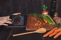 Woman following recipe on tablet and cooking healthy meal in the kitchen, cutting vegetables on the wooden table Royalty Free Stock Images