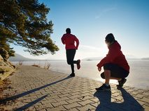Woman folowing running man at lake beach. Team of runners stock photography