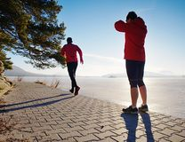 Woman folowing running man at lake beach. Team of runners stock image
