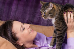 Woman fondles cat Royalty Free Stock Images