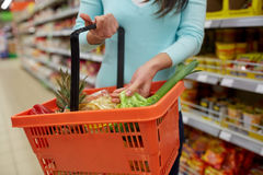 Woman with food basket at grocery or supermarket Royalty Free Stock Image