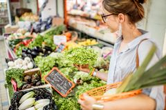 Woman at the food market. Young woman choosing a fresh salad standing with basket at the food market in France royalty free stock images