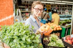 Woman at the food market. Young woman choosing a fresh tomato standing with basket at the food market in France royalty free stock photography