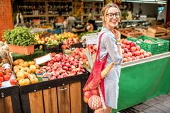 Woman at the food market. Young woman standing outdoors with mesh bag full of fresh vegetables in front of the food market stock photo
