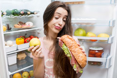 Woman with food near refrigerator. Young woman choosing between apple and big sandwich standing in front of the refrigerator full of vegetables and fruits Stock Photo