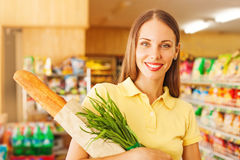 Woman food shopping. Woman buying bread and onion in supermarket, looking at camera Stock Photo