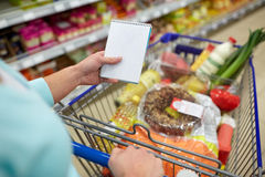 Woman with food in shopping cart at supermarket Royalty Free Stock Photography