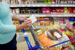 Woman with food in shopping cart at supermarket. Consumerism and people concept - woman with notebook and shopping cart or trolley buying food at grocery store Royalty Free Stock Images