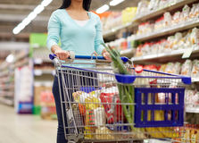 Woman with food in shopping cart at supermarket Stock Images