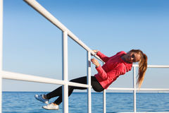 Woman fool around sitting on handrail near sea. Outdoor, dangerous play, sport concept. Woman in sports suit sitting on handrail next to sea and having fun while royalty free stock photo