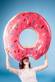 Woman fooling around with float ring in form of doughnut. Elderly woman fooling around with float ring in form of doughnut Royalty Free Stock Photography