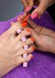 Woman foot in nail polishing Stock Photos