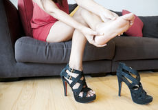 Woman With Foot Pain. Woman massaging her foot because of foot pain from waring high heels Royalty Free Stock Photography