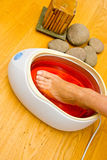 Woman foot in paraffin bath at the spa