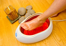 Woman foot in paraffin bath at the spa Stock Photos