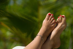 Woman foot with red pedicure in the tropical beach conceptual im Royalty Free Stock Photography