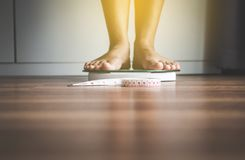 Woman foot standing on weigh scales with tape measure in foreground. In room stock images