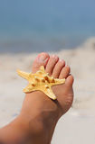 Woman foot with starfish, soft beach background Royalty Free Stock Images