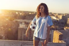 Woman in a football jersey holding a ball. Young woman wearing a football jersey standing on a building rooftop, holding a ball and watching a sunset over the Royalty Free Stock Photo