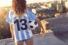 Woman in a football jersey. Young woman wearing a football jersey standing on a building rooftop, holding a ball and watching a sunset over the city. Focus on Royalty Free Stock Photos