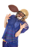 Woman football player hit in helmet with ball. A woman football player with a football stuck in her mask Royalty Free Stock Photo