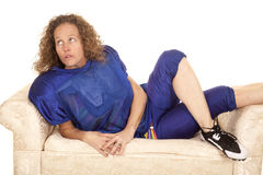 Woman football player lay on sofa. A woman in her football gear laying on a couch Stock Image