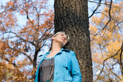 Woman in the forest. Woman at the blue raincoat in the forest Royalty Free Stock Image