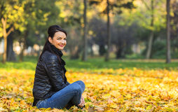 Woman in a Forest in the Autumn. Portrait of a young smiling woman in a yellow autumn forest Royalty Free Stock Image