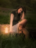 Woman in the forest with a lantern and a cat Stock Photo