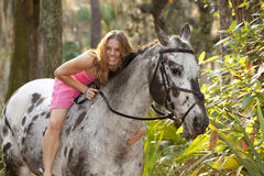 Woman in forest lying on horse Royalty Free Stock Image