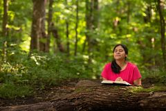 Woman in Forest Preserve with Bible Kneeling in Prayer. Hispanic Woman in Forest Preserve with Bible Kneeling in Prayer stock images