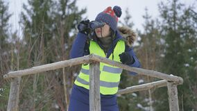 Woman forester on tower looking through binoculars in forest