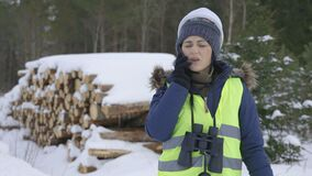 Woman forester using smartphone in winter forest
