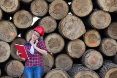 Woman forestry engineer beside trunks. Young woman forestry engineer talking on phone in front of trunks stock image