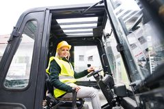 Woman forklift truck driver in an industrial area. Female forklift truck driver in an industrial area. A woman sitting in the fork lift outside a warehouse Royalty Free Stock Image