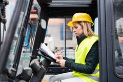 Woman forklift truck driver in an industrial area. Female forklift truck driver in an industrial area. A woman sitting in the fork lift outside a warehouse Royalty Free Stock Photos