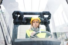 Woman forklift truck driver in an industrial area. Female forklift truck driver in an industrial area. A woman sitting in the fork lift outside a warehouse Royalty Free Stock Photography