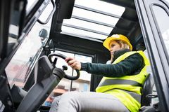 Woman forklift truck driver in an industrial area. Female forklift truck driver in an industrial area. A woman sitting in the fork lift outside a warehouse Royalty Free Stock Photo