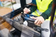 Woman forklift truck driver in an industrial area. Unrecognizable female forklift truck driver in an industrial area. A woman sitting in the fork lift outside a Royalty Free Stock Image
