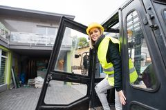 Woman forklift truck driver in an industrial area. A woman getting out of the fork lift truck Stock Photo