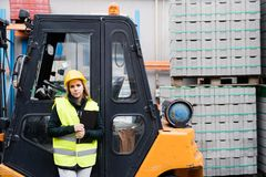Woman forklift truck driver in an industrial area. A woman standing in front of the fork lift truck outside a warehouse Royalty Free Stock Photography