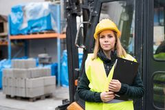 Woman forklift truck driver in an industrial area. A woman standing in front of the fork lift truck outside a warehouse Stock Photo